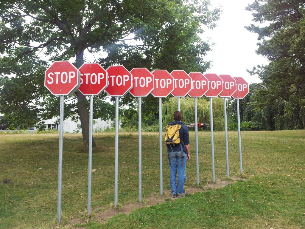 Series of overlapping signs labelled stop