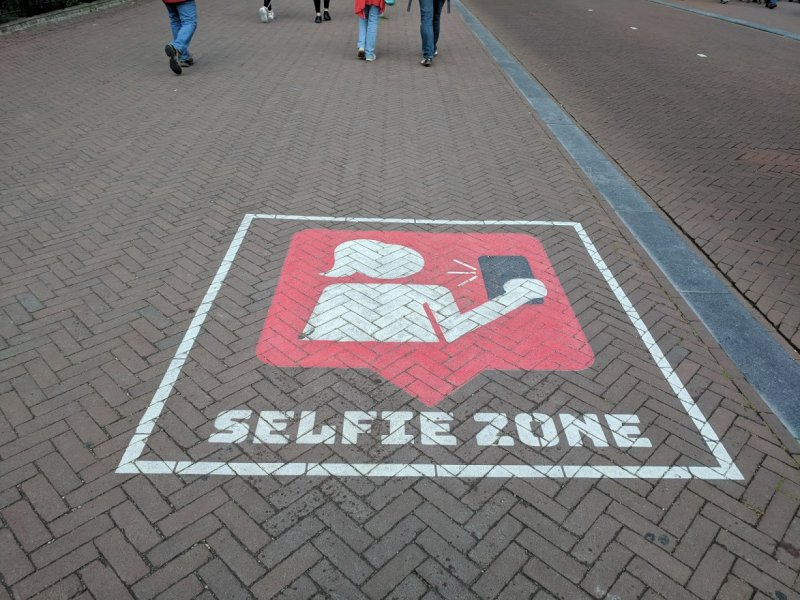 "Sign painted on footpath with an image of a person taking a selfie, labelled ""Selfie Zone"""