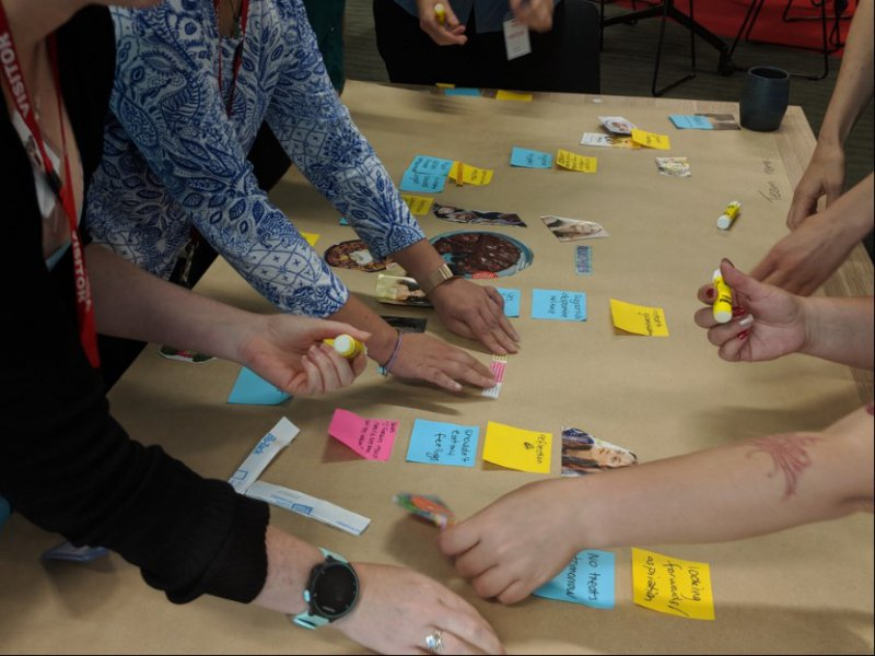 Hands moving post-it notes on a workshop table