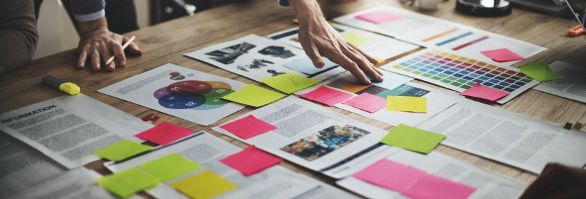 Documents and sticky notes scattered across a table